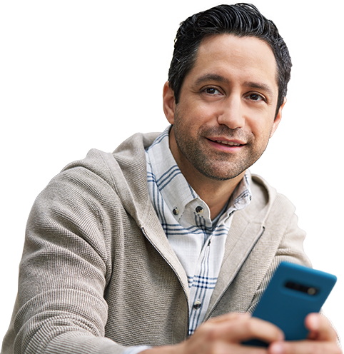 A young man holding his phone like he's about to use it, but looking outward and smiling.